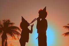 Partie de plage - le petit garçon et la fille jouent au coucher du soleil Image stock