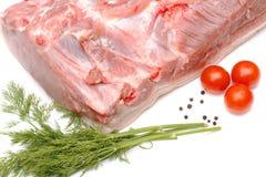 Partie de porc et de légumes sur le blanc Photo stock