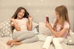 Partie de pyjama de fille de loisirs Smartphone de filles posant le grand tir Envoyez ? photo le r?seau social utilisant le smart photographie stock