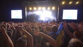 Partie de roche, admirateurs de foule ondulant des mains sur le concert de musique en direct contre l'étape allumée lumineuse ave banque de vidéos