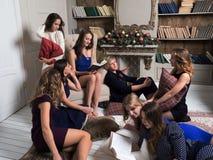 Partie du ` s de nouvelle année de belles filles Lecture commune des livres photo stock