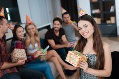 Partie en l'honneur de l'anniversaire Les invités donnent leurs cadeaux à la fille d'anniversaire La fille est très heureuse de r images libres de droits