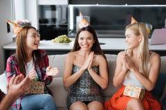 Partie en l'honneur de l'anniversaire Les invités donnent leurs cadeaux à la fille d'anniversaire La fille est très heureuse de r photo libre de droits