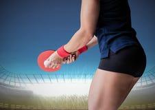 Partie inférieure du corps de joueur de ping-pong contre le stade avec les lumières lumineuses et le ciel bleu Photos stock