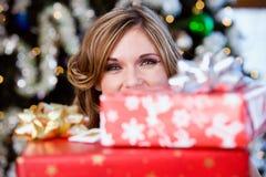 Partie : Jolie femme jetant un coup d'oeil par derrière les cadeaux Photographie stock