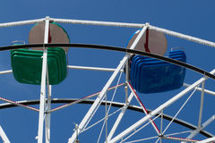 Partie supérieure de roue de ferris avec les cuvettes vertes et bleues Image stock