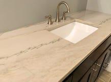 Partie supérieure du comptoir de granit avec le robinet blanc d'évier et de chrome sur les armoires en bois foncées, plancher de  images stock