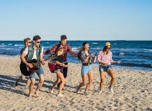 Partie sur la plage avec la guitare Amis dansant ensemble à la plage Images stock