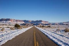 Partiellement la neige a couvert la route en hiver Photos libres de droits