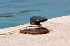Partiellement s'est rouillée la vieille borne forte d'amarrage de fer vissée sur le pilier en pierre local avec cinq boulons roui image libre de droits