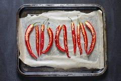 5 partieron en dos los chiles rojos en un molde para el horno Imagenes de archivo