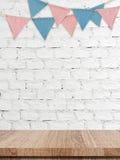 Partiflaggor som hänger på den vitt tegelstenväggen och trä, bordlägger backgroun Royaltyfri Fotografi