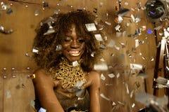 Partiflicka Förvånad ung afrikansk amerikankvinna i guld- makeup och tillbehör som ut sträcker händer medan konfettier som faller Arkivbild