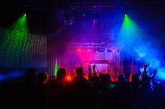 Partifolk som dansar i kulört ljus arkivbild