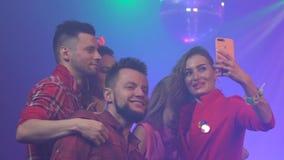 Partifolk som tar en selfie på nattklubben med musik i rökbakgrunden långsam rörelse lager videofilmer