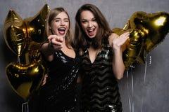 Partigyckel härliga fira flickor isolerade nytt över det vita året Stående av ursnygga le unga kvinnor som tycker om partiberöm arkivfoto