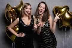 Partigyckel härliga fira flickor isolerade nytt över det vita året Stående av ursnygga le unga kvinnor som tycker om partiberöm arkivbild