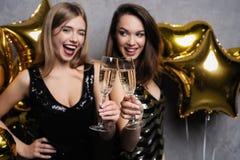 Partigyckel härliga fira flickor isolerade nytt över det vita året Stående av ursnygga le unga kvinnor som tycker om partiberöm arkivfoton