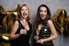 Partigyckel härliga fira flickor isolerade nytt över det vita året Stående av ursnygga le unga kvinnor som tycker om partiberöm royaltyfri fotografi