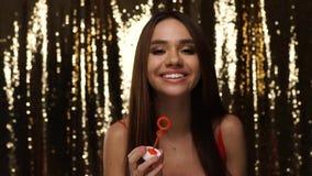 Partigyckel Kvinna som blåser såpbubblor på skinande guld- bakgrund stock video