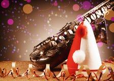 Partihatt, saxofon och banderoller på tabellen Arkivfoto