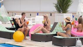 Partij in de jongeren van de poolgroep in zwempakken op chaise-longue met gekleurde dranken stock videobeelden