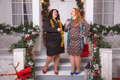 Partij en viering De wintervakantie Kerstmis plus Nieuwe het jaarmeisjes die van de groottevrouw op portiek blijven Sexy plus gro Stock Foto
