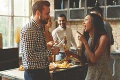 Partij met beste vrienden Groep vrolijke jongeren die huis van partij met snacks en dranken genieten terwijl het communiceren royalty-vrije stock afbeelding