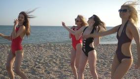 Partij op zee, bedrijf van meisjes in badpakken die pret hebben en op strand bij weekend dansen stock footage