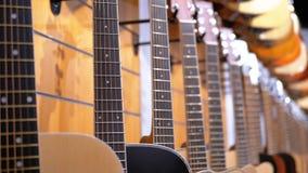 Partij van akoestische gitaren die in een muziekopslag hangen Winkel muzikale instrumenten stock video