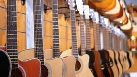 Partij van akoestische gitaren die in een muziekopslag hangen Winkel muzikale instrumenten stock videobeelden