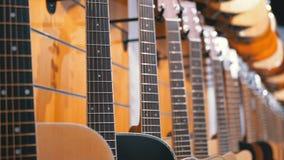 Partij van akoestische gitaren die in een muziekopslag hangen Winkel muzikale instrumenten stock footage