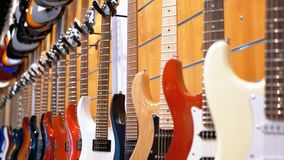 Partij van elektrische gitaren die in een muziekopslag hangen Winkel muzikale instrumenten stock footage