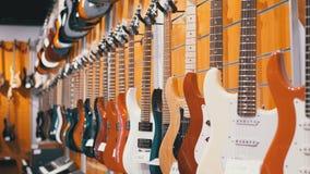 Partij van elektrische gitaren die in een muziekopslag hangen Winkel muzikale instrumenten stock videobeelden