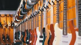 Partij van elektrische gitaren die in een muziekopslag hangen Winkel muzikale instrumenten stock video