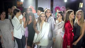 Partij van gelukkige glimlachende jonge groep mensen, de mooie vrienden van het modellenmeisje met discolichten in nachtclub voor stock video