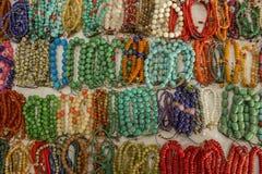 Partij van heldere die multi-colored armbanden van ballen van stenen wordt gemaakt die op de witte oppervlakte van de lijst ligge royalty-vrije stock foto