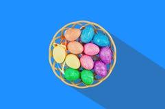 Partij van kleurrijke en fonkelende kunstmatige eieren in bruine rieten mand met lange harde schaduw in centrum van blauwe lijst  stock fotografie