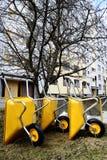 Partij van lege nieuwe gele tuinkruiwagens Stock Afbeelding