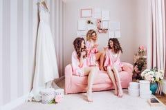 Partij voor meisjes De meisjes drinken roze champagne v??r de huwelijksceremonie in roze pyjama's royalty-vrije stock foto