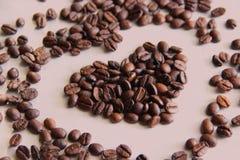 Partijen op de lijst geroosterde koffiebonen worden verspreid in de vorm van een hart dat stock afbeeldingen