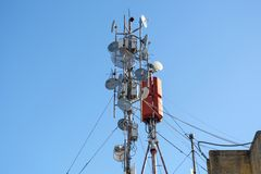 Partijenantennes van draadloos netwerk, telecommunicatie en satellietschotels op een de bouwdak stock afbeelding