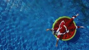 Partijkerstman in zwembad op watermeloenvlotter stock video