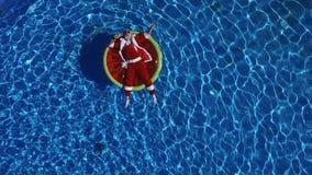 Partijkerstman in zwembad op watermeloenvlotter stock footage