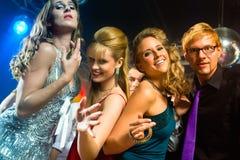 Partijmensen die in discoclub dansen Stock Foto's