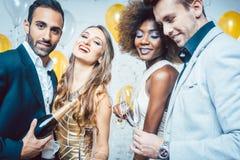 Partijmensen in een club vierende en gietende champagne royalty-vrije stock foto