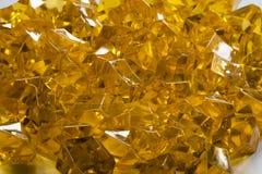 Partiklar av den genomskinliga gula plasten- i form av juvlar Royaltyfri Foto