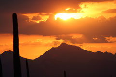 Parting Clouds. Orange sunset shinning through parting clouds over the desert mountains Stock Image