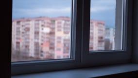 A partir de día a la vista nocturna a través de la ventana en las luces las ventanas en edificios altos almacen de video
