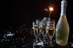 Partisammansättningsbild Exponeringsglas som fylls med champagne som förläggas på den svarta tabellen royaltyfri fotografi